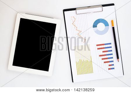 White office desk top with blank screen tablet pencil and chart or graph over backboard. Top view with copy space