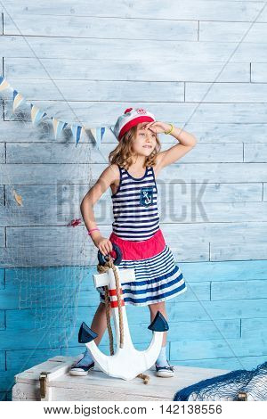 Little girl sailor standing and keeps anchor. Looking away
