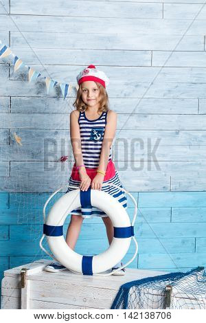 Little girl sailor standing and keeps lifebuoy. Looking at camera