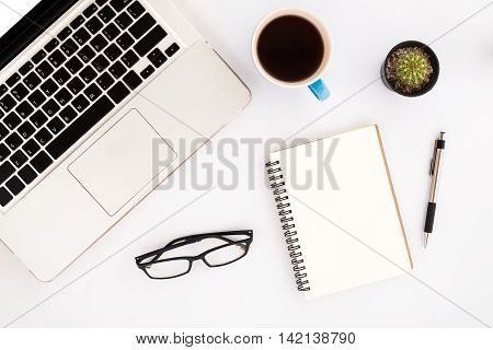 White office desk table with laptoppencilblank screen smartphoneleather notebookchart or graph and cup of coffee. Business desk table concept.Office supplies and gadgets on desk table.Flat lay photo.