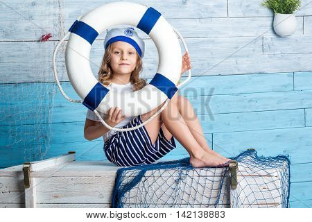 Little girl sailor sitting and keeps lifebuoy. Looking at camera