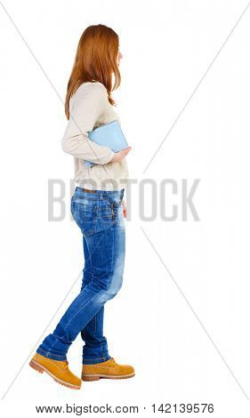 Girl comes with  stack of books. side view. Rear view people collection.  backside view of person.  Isolated over white background. The girl in a white blouse goes right with textbooks.
