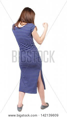 skinny woman funny fights waving his arms and legs. Isolated over white background. The brunette in a blue striped dress stands sideways and fighting with their fists.