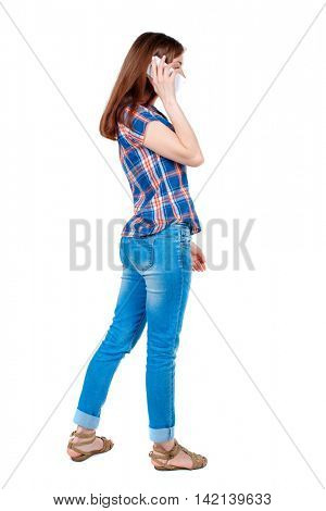 back view of a woman talking on the phone.  backside view of person.  Rear view people collection. Isolated over white background. Girl in plaid shirt standing sideways talking over the white