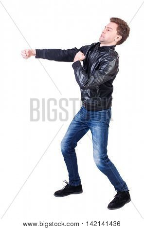 back view of guy funny fights waving his arms and legs. Isolated over white background. Rear view people collection.  backside view of person.Curly guy in a black leather jacket clumsily fighting.