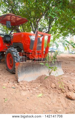 Tractor ploughing tree farm equipment in Thailand