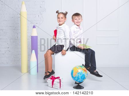 The students sit on a white background and the background of the large pencils . The concept of the day of knowledge