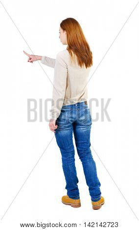 Back view of  pointing woman. beautiful girl. Rear view people collection.  backside view of person.  Isolated over white background. The girl in a white warm sweater showing with his right hand to