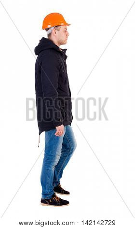 Back view of walking engineer in helmet.  Rear view people collection. Backside view of person. Isolated over white background. Engineer in warm clothes sadly goes to the right