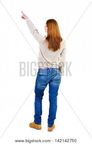 Back view of  pointing woman. beautiful girl. Rear view people collection.  backside view of person.  Isolated over white background. The girl in a white warm sweater shows an index finger upwards.
