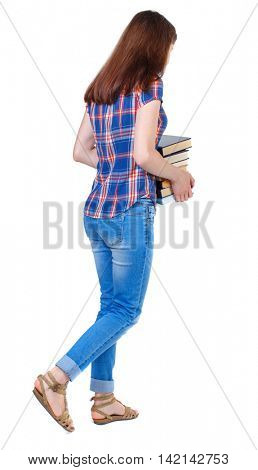 Girl comes with  stack of books. back side view. Rear view people collection.  backside view of person.  Isolated over white background. Girl in a plaid shirt goes the distance with textbooks.
