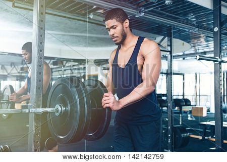 Afro american bodybuilder guy prepare to do exercises with barbell in a gym, keep barbell plate in hands