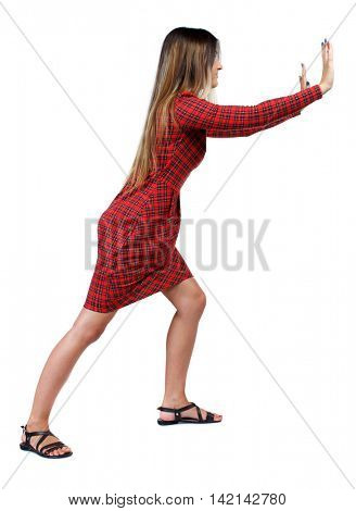 back view of woman pushes wall.  Isolated over white background. Rear view people collection. backside view of person. The girl in red plaid dress stands sideways and pushing his hands something to