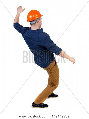 Balancing young man.  or dodge the falling man. worker in construction helmet falls. Rear view people collection.  backside view of person.  Isolated over white background. a man in a helmet is