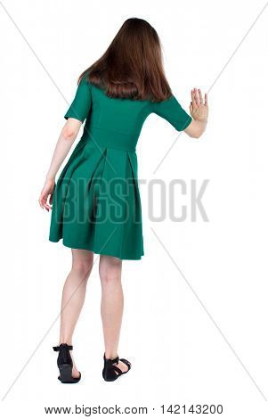 back view of woman. Young woman presses down on something. Isolated over white background. Rear view people collection. backside view of person. The slender brunette in a green short dress presses a