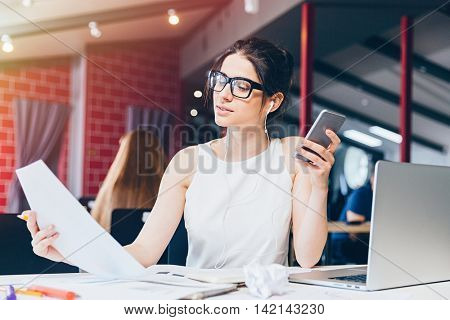 Attractive pensive young businesswoman working and listening to music from smartphone in office