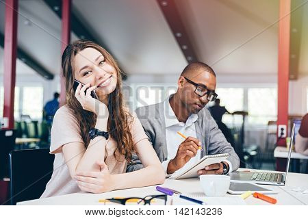 Cheerful beautiful young business woman talking on cell phone and working with serious african man in office