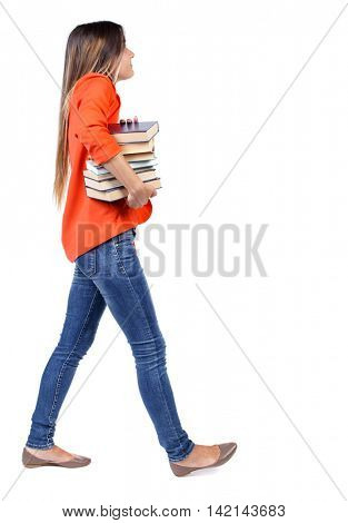 Girl comes with  stack of books. side view. Rear view people collection.  backside view of person.  Isolated over white background. student in a red jacket with difficulty carries a lot of books under