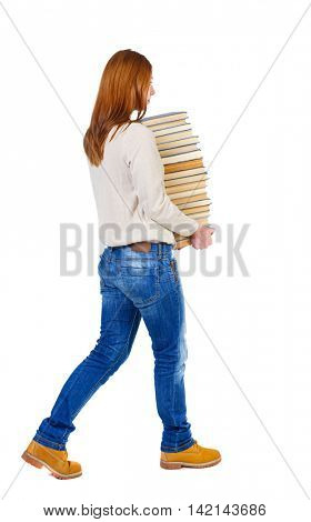 Girl comes with  stack of books. side view. Rear view people collection.  backside view of person.  Isolated over white background. The girl in a white warm jacket bears a huge stack of books