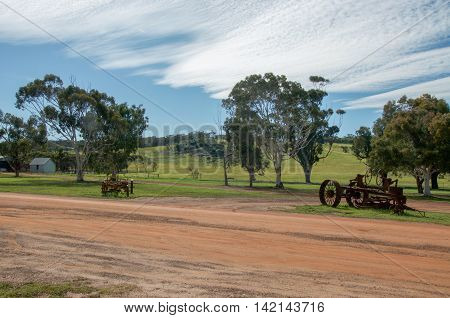 Old rusted antique farm machinery with red sand, manicured grass and native trees under a blue sky with clouds in rural farmland landscape in New Norcia, Western Australia.