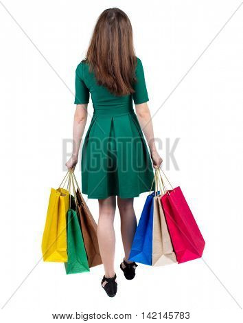 back view of woman with shopping bags. backside view of person.  Rear view people collection. Isolated over white background. The slender brunette in a green short dress is holding shopping bags.