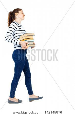 Girl comes with  stack of books. side view. Rear view people collection.  backside view of person.  Isolated over white background. Girl in a striped sweater goes to the side while holding heavy books