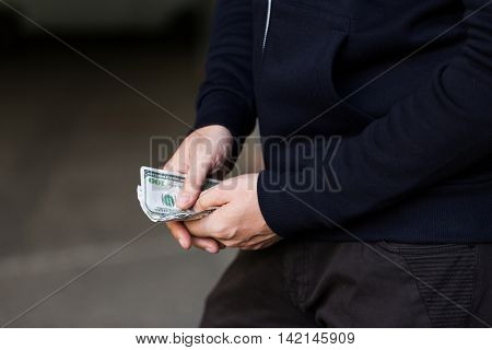 drug trafficking, finances, addiction, people and sale concept - close up of addict or dealer hands with dollar money