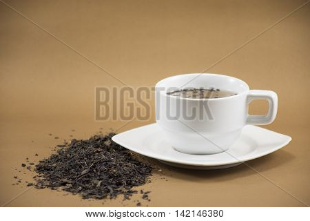White Tea cup and dry leave tea on brown background.