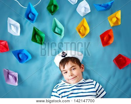 seven years old boy playing in sailor hat. Child withpaper ships on blue background