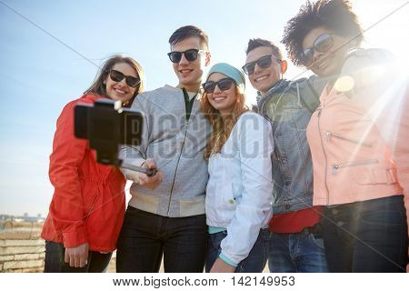 tourism, travel, people, leisure and technology concept - group of smiling teenage friends taking selfie with smartphone and monopod on city street