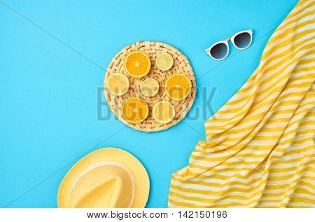 Fashion. Summer Beach set. Tropical Fruit Citrus Orange Lime. Bright Summer Color. Stylish woman Sunglasses Trendy hat. Essentials creative art. Minimal concept. Top view. Yellow blue background
