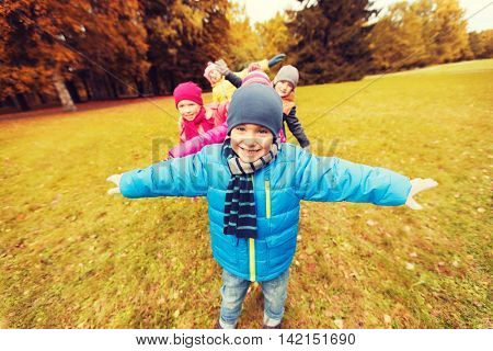 autumn, childhood, leisure and people concept - group of happy little children playing planes outdoors