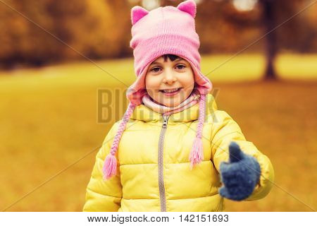 autumn, childhood, happiness, gesture and people concept - happy beautiful little girl showing thumbs up outdoors