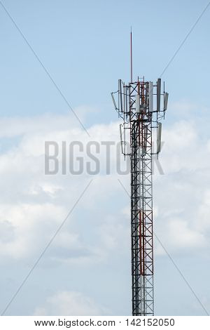 Top part of cell phone communication tower with multiple antennas and solar panels that supply of electricity against blue sky