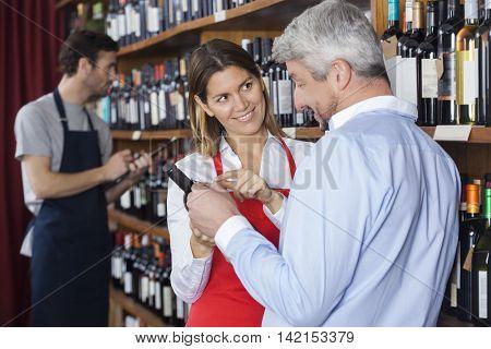 Smiling Saleswoman Showing Wine Bottle To Customer