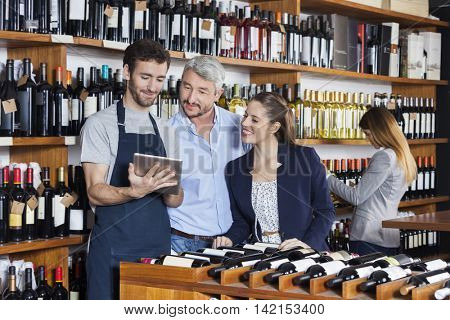 Salesman Showing Wine Information To Customers On Tablet Compute