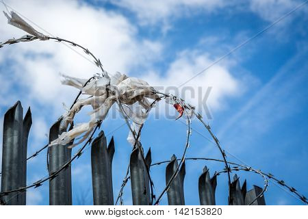 Barbed wire with rags, plastic and cloth against blue sky.