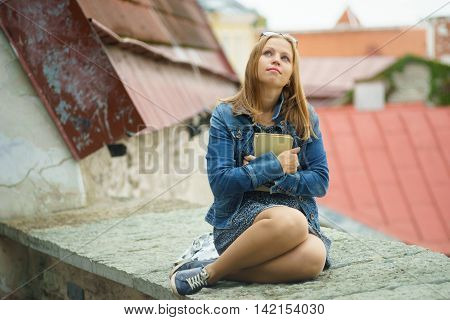 Romantic young woman sitting with book on viewing platform against city roofs
