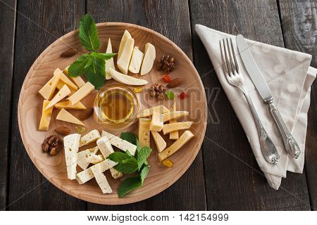 Cheese plate with honey and cutlery on wooden background. Restaurant serving of snack for wine