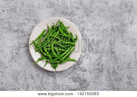 French bean in white plate on the rough light gray surface with copy space top view
