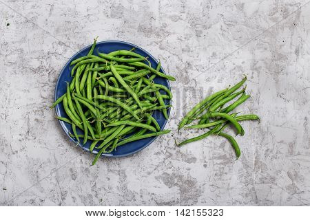 French bean in blue plate on the rough light gray surface top view
