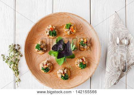 Foie gras plate on white wooden background, flat lay. Delicious french delicatessen on crackers, served on catering board. Wedding, celebration, luxury expensive food