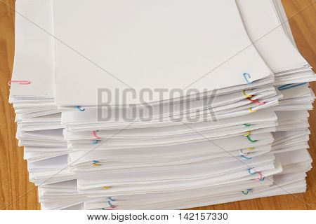 Colorful Paper Clip With Pile Of Overload Document And Reports