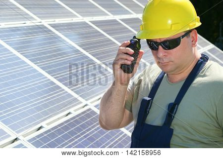 Green energy solar panels and worker with walkie talkie