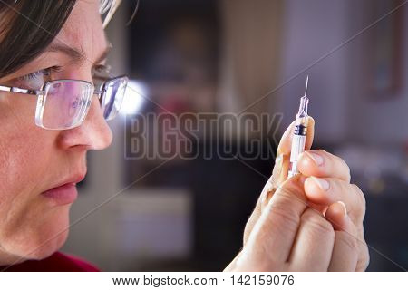 Adult woman preparing the syringe for injection. Intravenous therapy. Diabetic therapy. Insulin