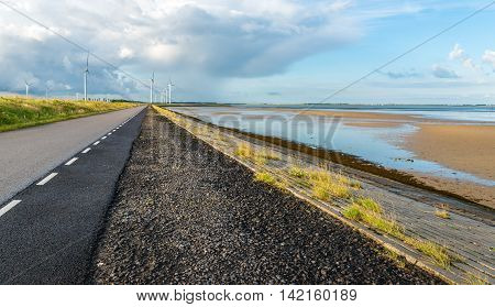 Long asphalt road on an embankment along an estuary in the Netherlands. In the background is a large wind farm. It is early in the morning in the summer season.
