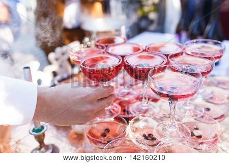 Hands with glasses of vine at the open air wedding banquet