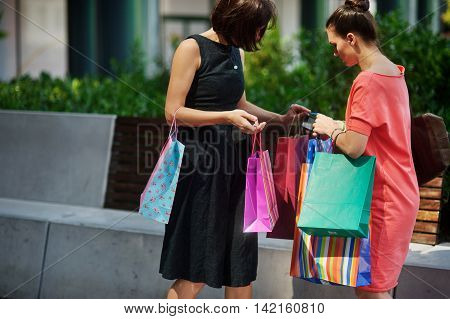 Two young women standing near the store. They are holding a lot of colorful shopping bags. Tired ladies recount packages.