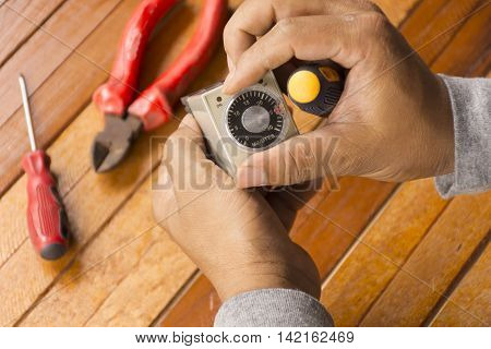 Timer tool with screwdriver in hand of man cleaning on wooden background.1