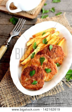 Minced meat cutlets and deep fried potatoes on a plate, a fork, a parsley leaves and burlap on old wood background. Cakes made with Turkey fillets and fried in vegetable oil. Recipe photo. Closeup